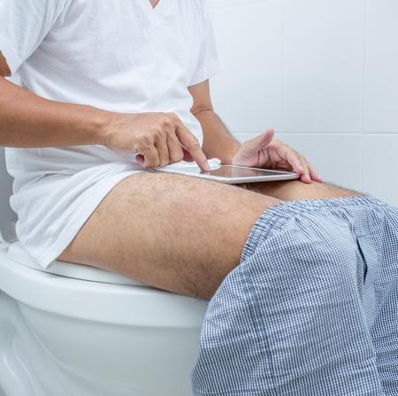 diarrea: hombre de trabajo con tableta digital mientras se est� sentado en el inodoro Foto de archivo