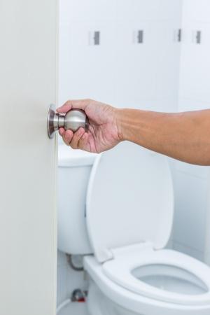door knob: Man hand open toilet door