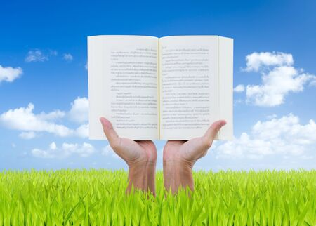 Man hands holding book on green field with blue sky background photo