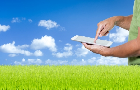 Man working with digital tablet on green grass and blue sky background photo