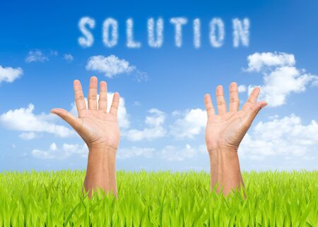 Two open hand with clouds solution word over green field and blue sky background photo