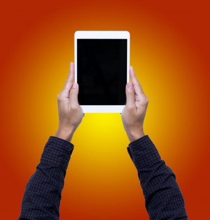 Man hands hold digital tablet isolated on orange background Stock Photo - 21685428