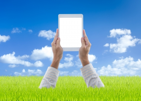 Man hands holding white digital tablet on green grass with blue sky background Stock Photo - 21685599