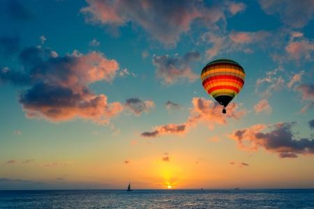 Hete lucht ballon met zonsondergang op de achtergrond van de zee