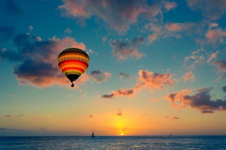 Pallone ad aria calda con il tramonto sullo sfondo del mare