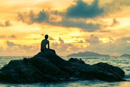 mind body soul: L'uomo seduto sulla roccia in spiaggia con lo sfondo del tramonto Archivio Fotografico
