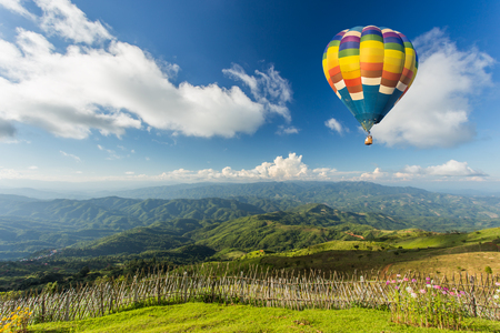 hot day: Colorful hot air balloon over the mountain Stock Photo