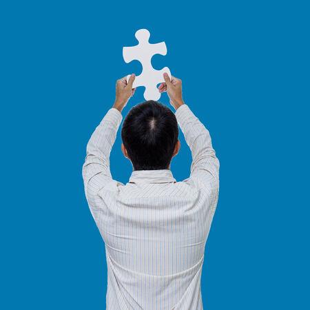 Business man holding jigsaw on green screen photo
