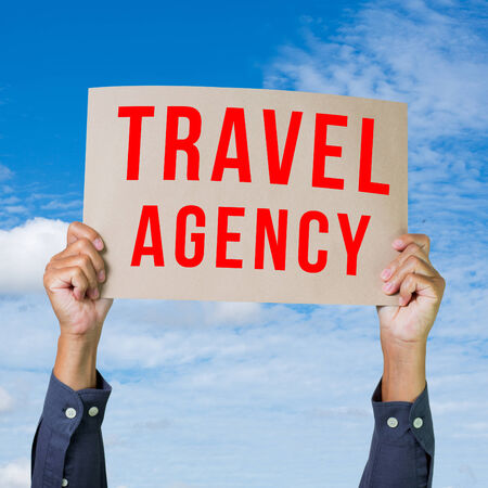 Man hand holding paper with travel agency word photo
