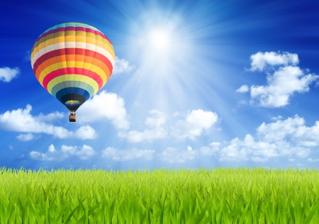 air view: Colorful hot air balloon over green field with sun beam background