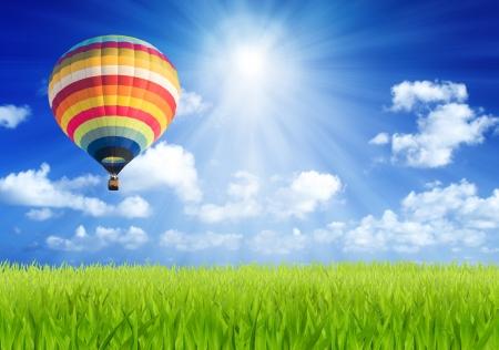 Kleurrijke hete luchtballon over groen gebied met zon balk achtergrond