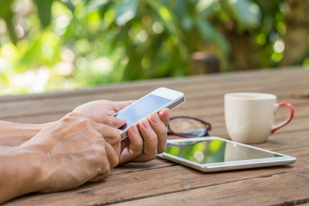 mobile: Man hands working on  smartphone with garden background