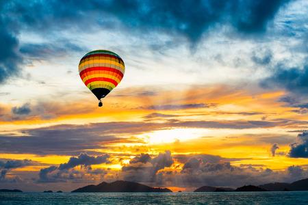 Hete luchtballon over de zee bij zonsondergang