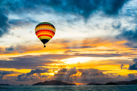 Hot air balloon over the sea at Sunset photo