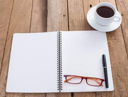 write us: Blank notebook with coffee cup on old wooden background