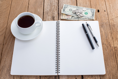 Blank notebook with pen and coffee cup on old wooden background photo