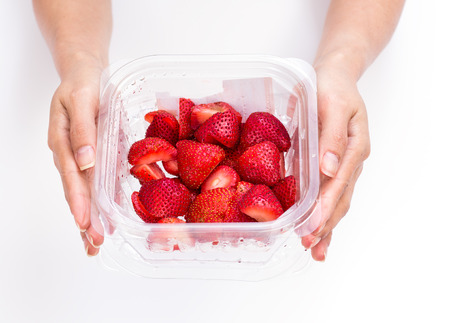 Women hands holding box of strawberry on wihte background photo