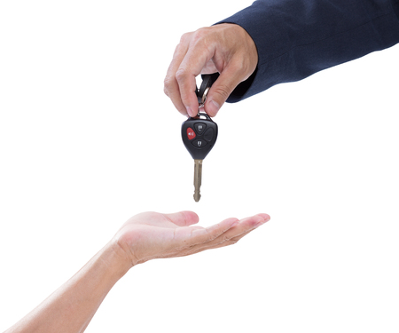 business man handing giving car remote keys to a casual senior man, isolated on white. clipping path photo