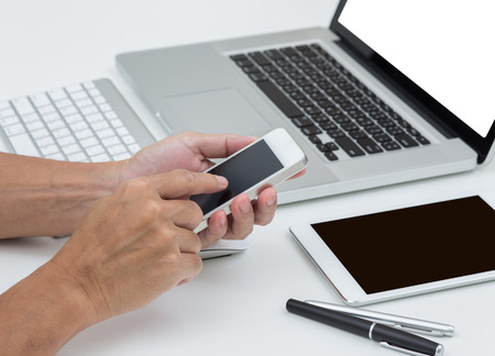 Man hands holding smart phone with laptop computer background photo