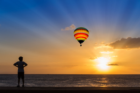 over the sea: Silhouette man and hot air balloon at sunset over ocean Stock Photo