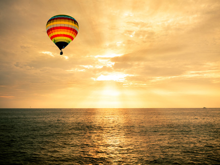 熱気球、夕焼けの海に