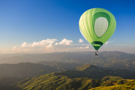 Green hot air balloon over the mountain at sunset photo