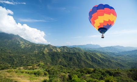 caliente: Globo de aire caliente sobre la montaña y el cielo azul de fondo