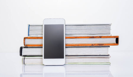 Mobile phone beside group of book on white background photo