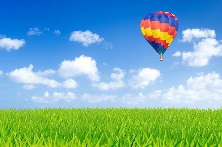 Colorful hot air balloon over green fields 写真素材
