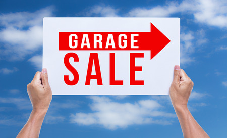 garage sale: Two hands holding brown cardboard with garage sale on blue sky background Stock Photo