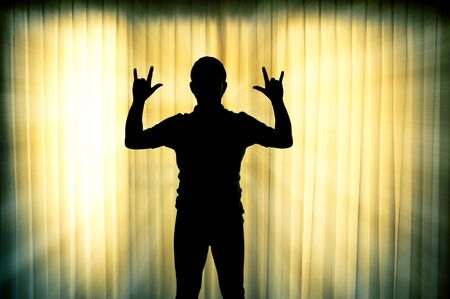 i love you sign: Silhouette man show his hands i love you sign with light ray effect