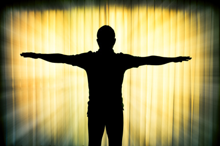 catholic cross: Silhouette man showing his hands like a cross with light ray effect Stock Photo