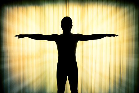 praise god: Silhouette man showing his hands like a cross with light ray effect Stock Photo