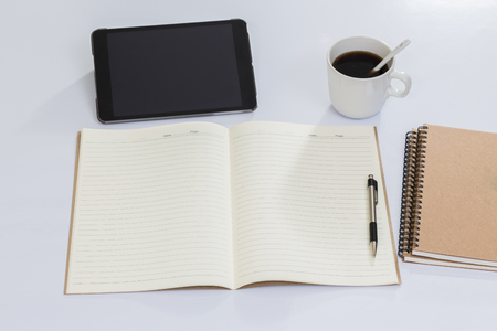 Blank notebook and office accessories on white table photo