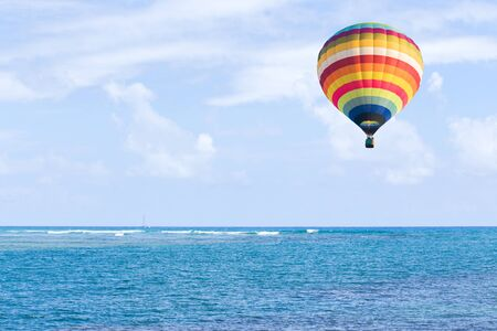 Hot air balloon over ocean and clouds blue sky