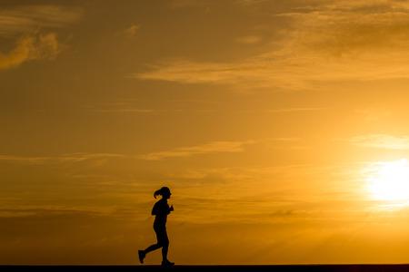 atleta corriendo: Las mujeres de la silueta de jogging al atardecer