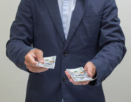 loaning: Businessman with hands giving dollar banknote, US dollars