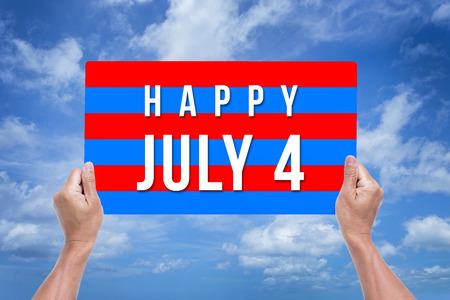 Man hands holding Happy July 4 banner with blue sky background