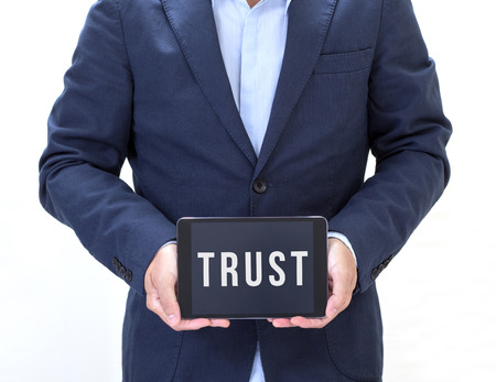 trust: Businessman hand holding tablet computer with trust on screen Stock Photo