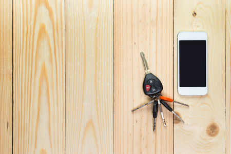 Mobile phone and car remote keys on wooden background