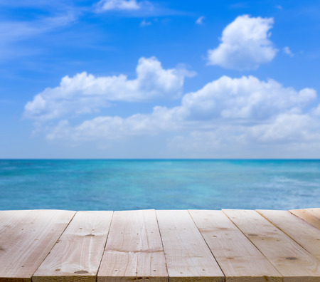 sunny beach: Wood table with blur  seascape and blue sky background