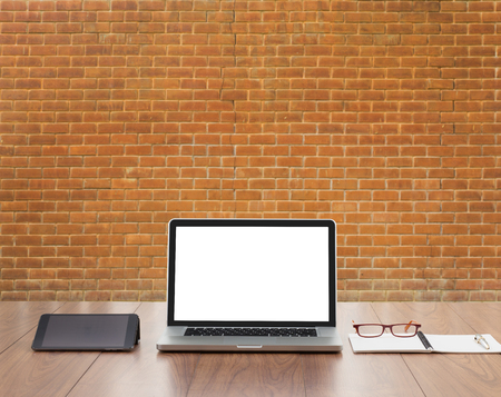 old desk: Blank screen laptop computer with red brick wall background Stock Photo