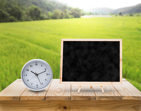 time table: blackboard adn clock on wood table top with blur green rice fields background