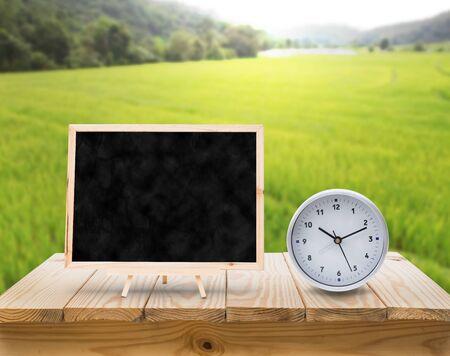adn: pizarra reloj del ADN en la mesa de madera de la parte superior con el desenfoque de campos verdes del arroz fondo Foto de archivo