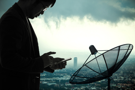 Strom: Businessman using smartphone with Satellite dish and strom clouds over big city background