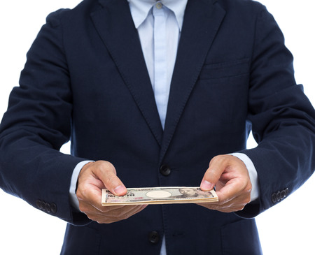 pay money: Businessman hand holding Japanese Yen Stock Photo