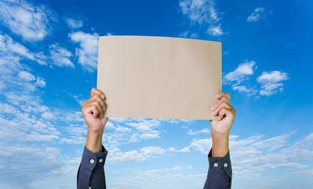annoucement: Businessman hands holding paper on blue sky background