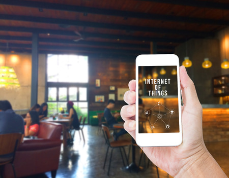 internet: Hand holding mobile phone with Internet of things word with blur coffee shop background,Digital Marketing concept Stock Photo