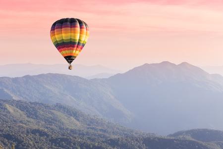 Hete luchtballon boven de hoge bergen bij zonsondergang