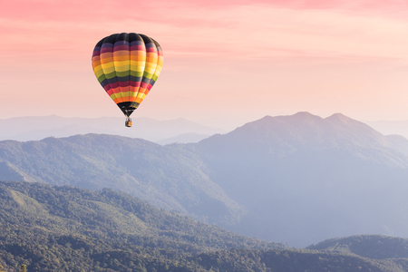 on air: Hot air balloon above high mountain at sunset